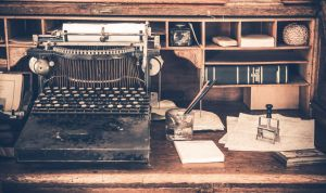 Old Desk Vintage Typewriter:desk, desktop, room, typing machine, typewriter, typing, author, writer, vintage, history, aged, lamp, dark, interior, workplace, furniture, calculating, bank, banking, accountant, accounting, old, nostalgia, wood, wooden, home, chair, business, horizontal