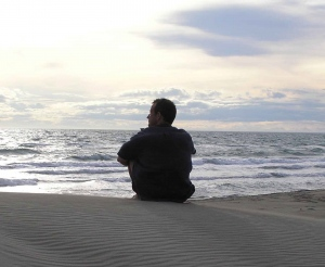 man-sitting-on-ocean-beach-solitude