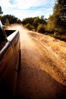 Truck-driving-down-dirt-road