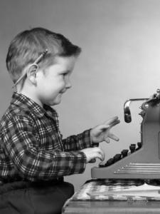 1950s-smiling-young-boy-typing-on-typewriter